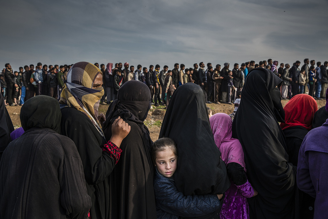 Civilians who had remained in west Mosul after the battle to take the city line up for aid in the Mamun neighbourhood. One girl turns her face to the masses while the others look on. Shot by Ivor Prickett.